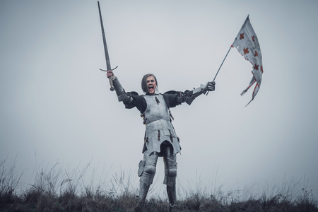 Foto de Girl in image of warrior stands in armor and issues battle cry with sword raised up and flag in her hands against background of sky and dry grass. - Imagen libre de derechos
