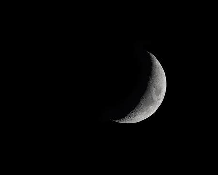 Foto de Waxing Crecent Moon Phase isolated on black - Imagen libre de derechos