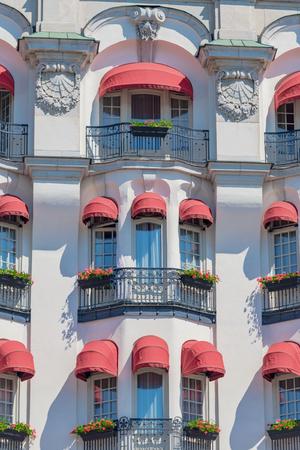 Foto de STOCKHOLM, SWEDEN 29 JUNE, 2019. Red colorful blinders at the white ornamented hotel Diplomat with french balconys facing Strandvägen in Stockholm during summer. - Imagen libre de derechos