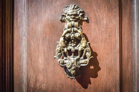 Photo pour old wooden door with decorated brass knocker - image libre de droit
