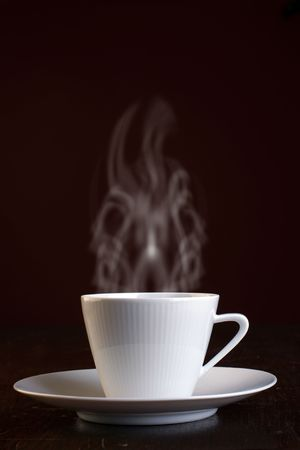 Cup of steaming hot coffee over dark background.