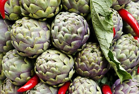 artichokes and red peppers on a market desk in rome