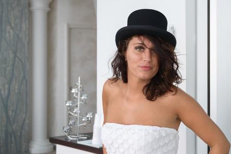 Foto de A nice girl in white posing with a black hat - Imagen libre de derechos