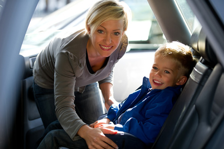 Mother fastening his son\'s seat belt