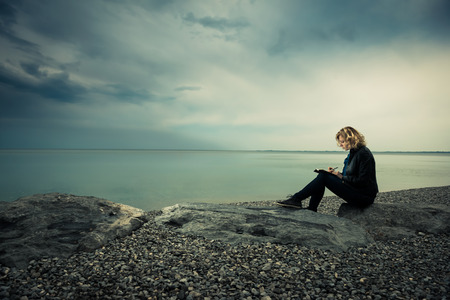 Photo pour Woman writing her thoughts or poetry by the sea - image libre de droit