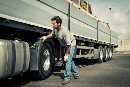 Photo for Truck driver working on truck tires - Royalty Free Image