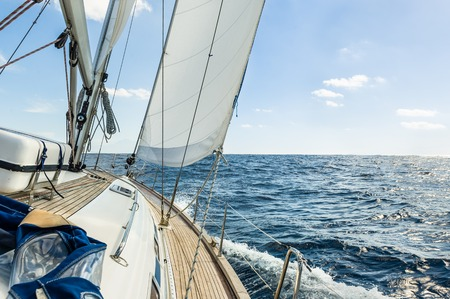 Foto per Sailing boat deck with hoisted sails and teak deck - Immagine Royalty Free
