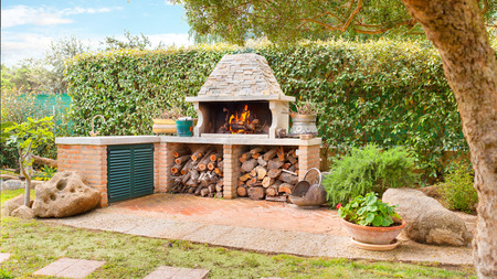 Foto de External Wood oven with burning fire and firewood - Imagen libre de derechos