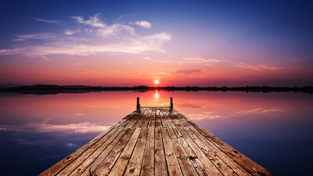 Photo for Perspective view of a wooden pier on the pond at sunset with perfectly specular reflection - Royalty Free Image