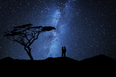 Photo for Couple of lovers silhouette kissing near a tree under a sky full of stars - Royalty Free Image