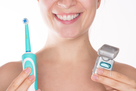 Foto de Young beautiful woman with a nice smile holding together an electric toothbrush and dental floss, isolated over a white background - Imagen libre de derechos