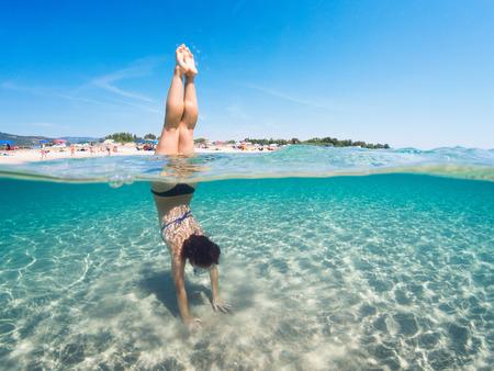 Foto de Young girl doing the vertical half underwater on a turquoise sea . Half underwater photography. - Imagen libre de derechos