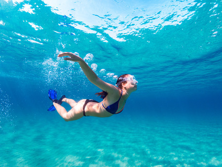 Foto de Young girl with mask and fins diving undewater on a clean blue sea. - Imagen libre de derechos