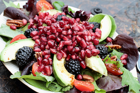 Photo pour A healthy salad with pomegranate, avocado, tomatoes, almonds and argula lettuce over a rustic background.  - image libre de droit
