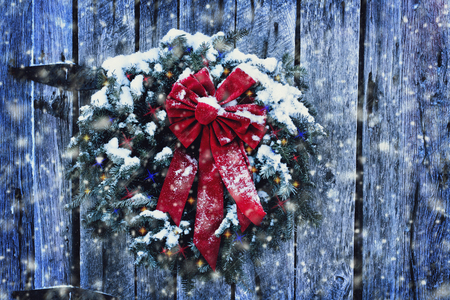 Photo for Rustic Christmas wreath on old weathered door with Christmas lights in a snow storm. - Royalty Free Image