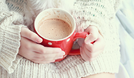 Photo pour Hands holding a vibrant red cup of hot chocolate. Extreme shallow depth of field. - image libre de droit