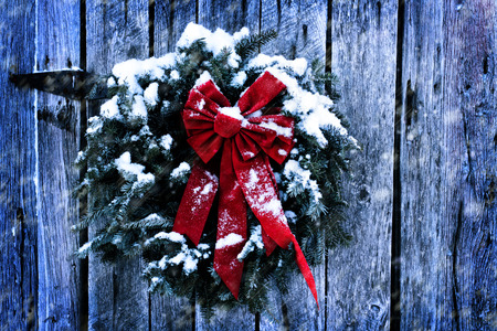 Photo pour Rustic Christmas wreath on old weathered barn in a snow storm. - image libre de droit