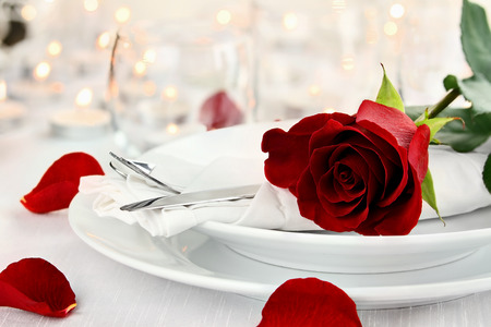 Photo pour Romantic candlelite table setting with long stem red rose. Shallow depth of field with selective focus on rose. - image libre de droit