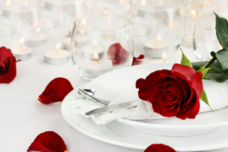 Photo for Romantic table setting with long stem red rose and candles burning in the background. Shallow depth of field with selective focus on rose. - Royalty Free Image