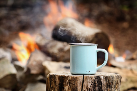 Foto de Blue enamel cup of hot steaming coffee sitting on an old log by an outdoor campfire. Extreme shallow depth of field with selective focus on mug. - Imagen libre de derechos