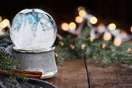 Photo pour Rustic image of a snow globe surrounded by pine branches, cinnamon sticks and a warm gray scarf. Shallow depth of field with selective focus on snowglobe. - image libre de droit