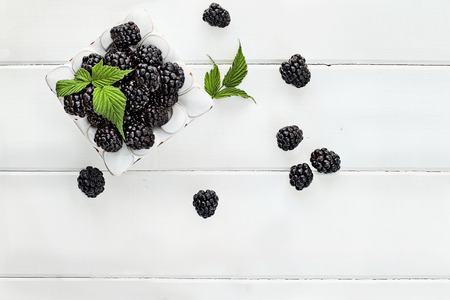 Photo for Overhead shot of fresh blackberry fruit over white wood table top. Room for copy space. - Royalty Free Image
