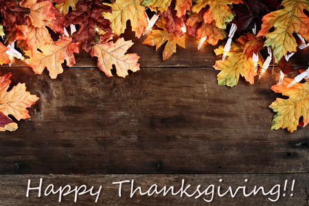 Foto de Rustic fall background of autumn leaves and decorative lights with Happy Thanksgiving text over a rustic background of barn wood. Image shot from overhead. - Imagen libre de derechos