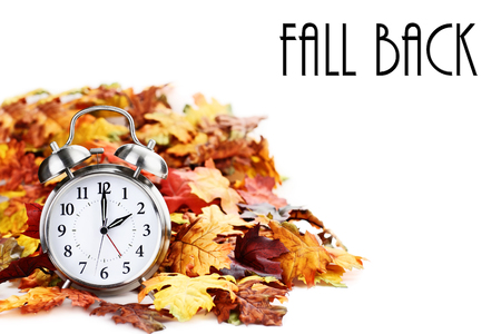 Photo pour Alarm clock in colorful autumn leaves isolated against a white background with light shadow and shallow depth of field. Daylight savings time concept. - image libre de droit