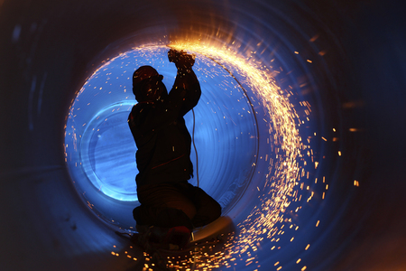 Photo pour A worker works inside a pipe on a pipeline construction - image libre de droit