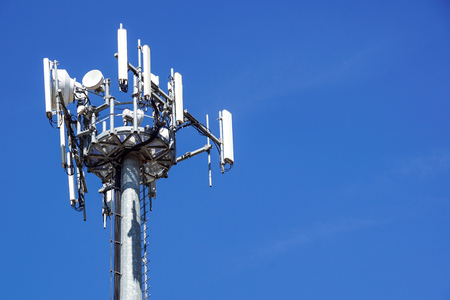 Photo for Top part of cell phone communication tower with multiple antennas against a blue sky - Royalty Free Image
