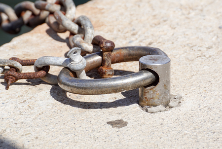 Photo for Old metal rusty mooring bollard with a chain - Royalty Free Image