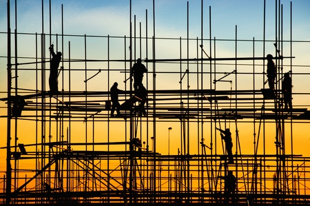 Photo for Construction site, silhouettes of workers against the light/ - Royalty Free Image
