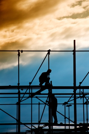 Photo for Construction site, silhouettes of workers against the light  - Royalty Free Image