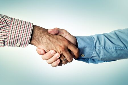 Two businessmen shaking hands, common greeting ritual