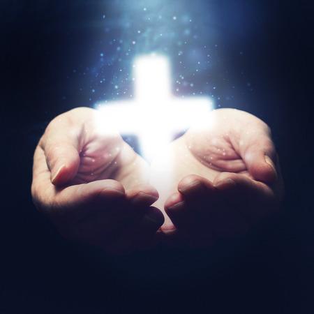 Foto de Open hands holding cross, symbol of Christian faith - Imagen libre de derechos