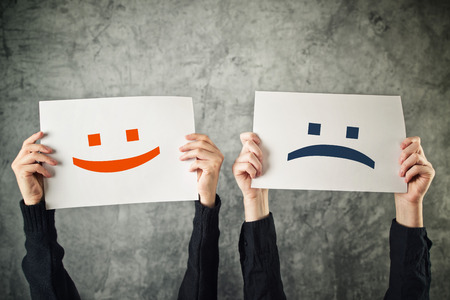 Photo for Happy and sad face. Women holding papers with happy and sad emoticons. - Royalty Free Image