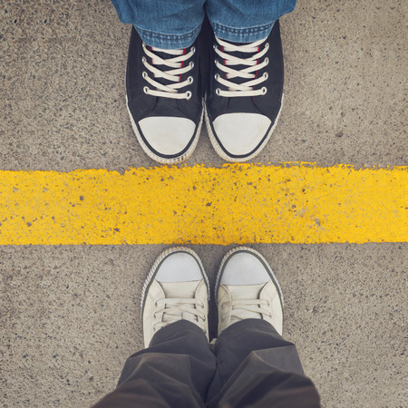 Photo pour Sneakers from above. Male and female feet in sneakers from above, standing at dividing line. - image libre de droit