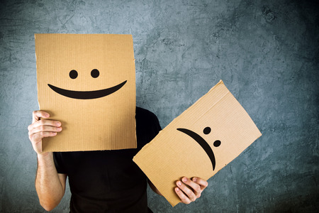 Photo pour Man holding cardboard paper with happy smiley face printed on. Happiness and joy concept. - image libre de droit