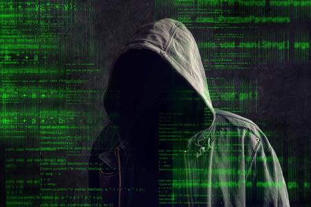 Foto de Faceless hooded anonymous computer hacker with programming code from monitor - Imagen libre de derechos