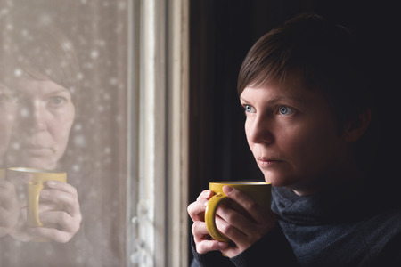 Photo pour Lonelsome woman drinking cup of coffee by the window of her living room, looking out at snow falling with a sad look on her face. Selective focus with shallow depth of field. - image libre de droit