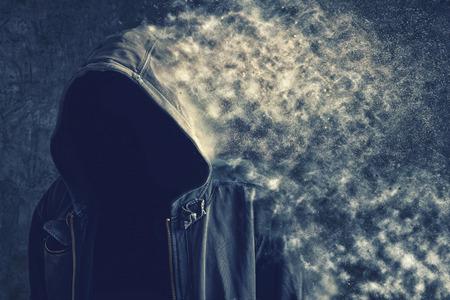 Foto de Faceless unknown and unrecognizable man without identity disintegrating and vanishing into the dust particles, life dissolving concept. - Imagen libre de derechos