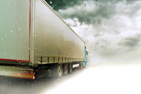 Photo for Speeding Transportation Truck driving on the road through the Snow Winter Scenery - Royalty Free Image