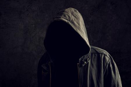 Foto de Faceless unknown and unrecognizable man without identity wearing hood in dark room, spooky criminal person. - Imagen libre de derechos