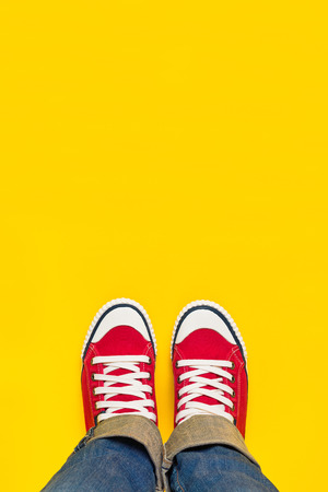 Photo pour Feet From Above Concept, Teenage Person in Red Sneakers Standing on Yellow Background, B;lank Copy Space in Front. - image libre de droit