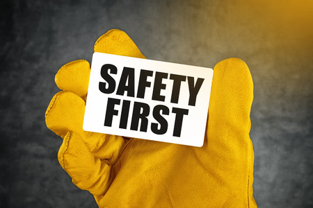 Photo pour Safety First on Business Card, Male Hand in Yellow Leather Construction Working Protective Gloves Holding Card with Rounded Corners. - image libre de droit