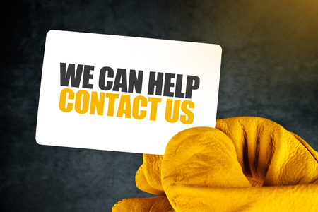 Foto de We Can Help, Contact Us on Business Card, Male Hand in Yellow Leather Construction Working Protective Gloves Holding Card with Rounded Corners. - Imagen libre de derechos