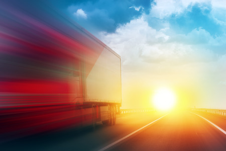 Photo pour Speeding Transportation Delivery Truck on Open Highway with Sun Settimg Down on Horizon in Background. - image libre de droit