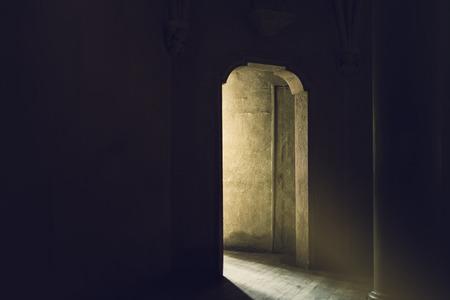 Foto de Mystic Gothic Door with Sunlight Entering Dark Room, Exit to Light, Hope and New Beginning Concept, Vintage Retro Tone Effect - Imagen libre de derechos