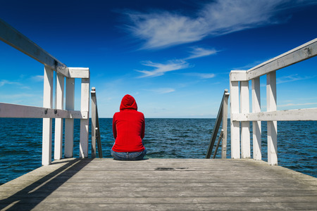 Foto de Alone Young Woman in Red Hooded Shirt Sitting at the Edge of Wooden Pier Looking at Water - Hopelessness, Solitude, Alienation Concept - Imagen libre de derechos