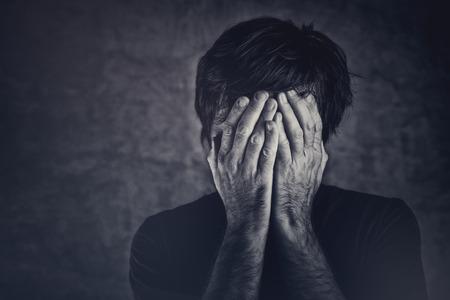 Foto de Grief, man covering fsce and crying, monochromatic image - Imagen libre de derechos